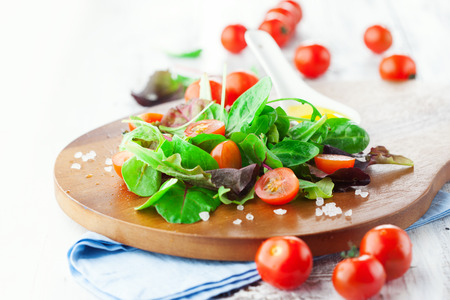 Fresh salad with cherry tomatoes, spinach, arugula, romaine and lettuce on a wooden chopping board on rustic white background, selective focus 스톡 콘텐츠