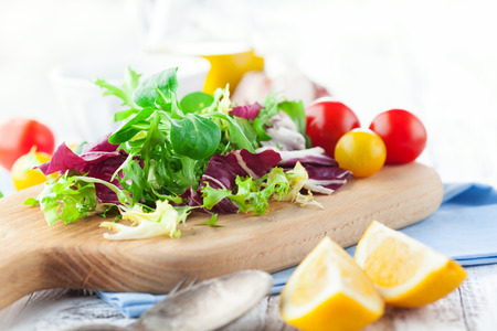 vegetable garden: Fresh salad with cherry tomatoes, spinach, arugula, romaine and lettuce on a wooden chopping board on rustic white background, selective focus Stock Photo