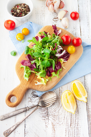 Fresh salad with cherry tomatoes, spinach, arugula, romaine and lettuce on a wooden chopping board on rustic white background, selective focus 免版税图像