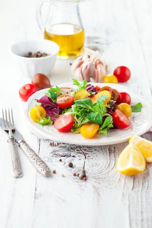チェリー トマト、ほうれん草、ルッコラ、ロメイン レタス、白い木製の背景にあるプレートのレタスのサラダ 写真素材