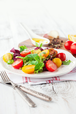 Fresh salad with cherry tomatoes, spinach, arugula, romaine and lettuce in a plate on white wooden background