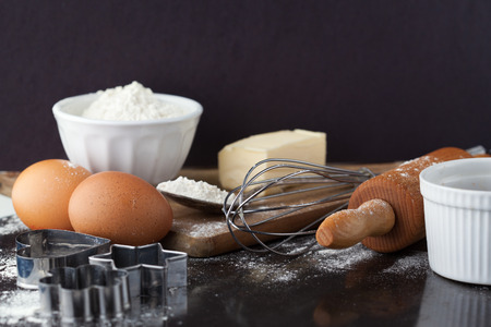 Baking cake ingredients with raw eggs, rolling pin, flour and cookie cutters on black background Stockfoto