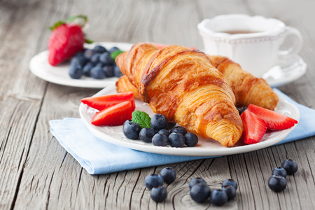 Delicious breakfast with fresh croissants and ripe berries on old wooden background, selective focus