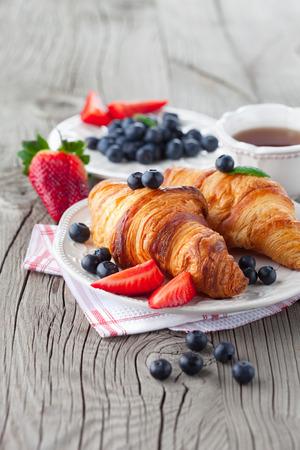 焼きたてのクロワッサン、古い木製の背景、選択と集中で熟した果実とおいしい朝食 写真素材
