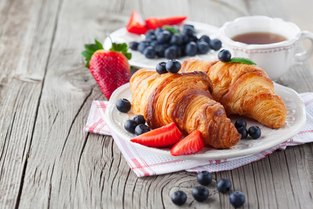 french bread rolls: Delicious breakfast with fresh croissants and ripe berries on old wooden background, selective focus