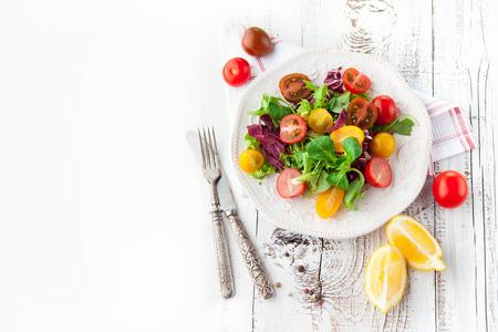 lechuga: Ensalada fresca con tomates cherry, espinacas, rúcula, lechuga romana y lechuga en un plato sobre fondo blanco de madera, vista desde arriba