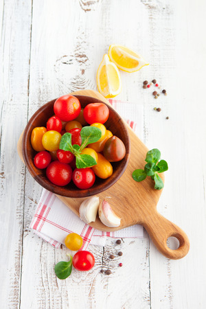 Fresh cherry tomatoes with basil leaves in a bowl on white wooden background, selective focus