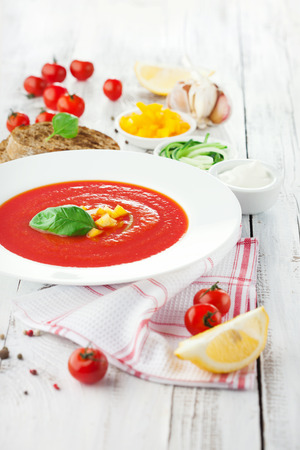 Tomato soup gazpacho and ingredients on white wooden background, selective focus photo