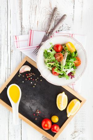 チェリー トマト、ほうれん草、ルッコラ、ロメイン レタス、白い木製の背景、上面のプレートでレタスとサラダ 写真素材