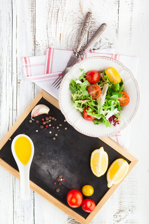 Fresh salad with cherry tomatoes, spinach, arugula, romaine and lettuce in a plate on white wooden background, top view