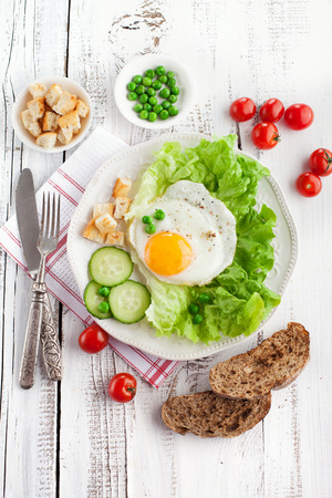 english cucumber: Breakfast with fried egg, vegetables and croutons on white wooden background, top view