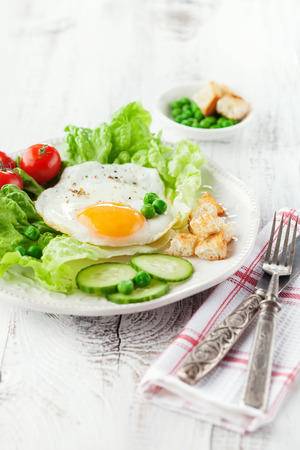 Breakfast with fried egg, vegetables and croutons on white wooden background, selective focus