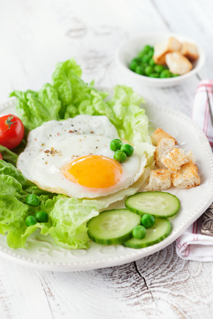 english cucumber: Breakfast with fried egg, vegetables and croutons on white wooden background, selective focus