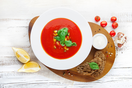 Tomato soup gazpacho and ingredients on white wooden background, top view