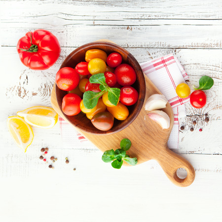 Fresh cherry tomatoes with basil leaves in a bowl on white wooden background, top view