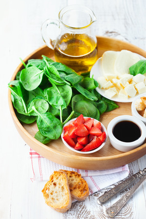 raw food: Fresh summer salad with strawberries, spinach leaves and feta cheese on white wooden background, selective focus