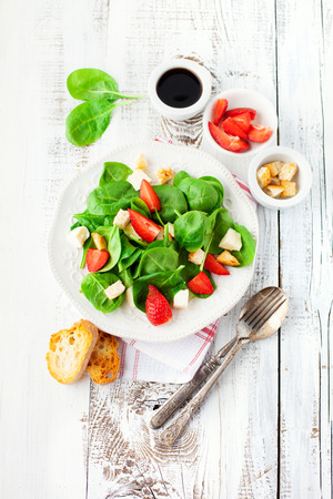 Fresh summer salad with strawberries, spinach leaves and feta cheese on white wooden background, top view Stockfoto