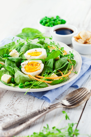 salad in plate: Fresh summer salad with green beans, spinach leaves and eggs on white wooden background, selective focus Foto de archivo