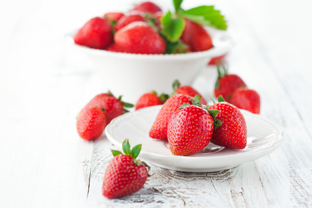 Juicy fresh strawberries in a bowl on a white wooden background, selective focus