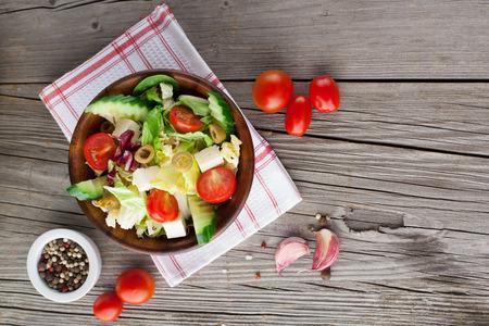ensalada de tomate: Ensalada fresca del verano con tomates cherry, espinacas, rúcula, lechuga romana y lechuga en el fondo de madera oscura, vista superior