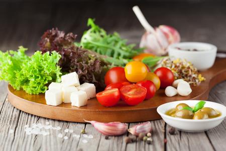 チェリー トマト、ほうれん草、ルッコラ、ロメイン レタス、暗い木製の背景、選択と集中にレタスと新鮮な夏サラダ