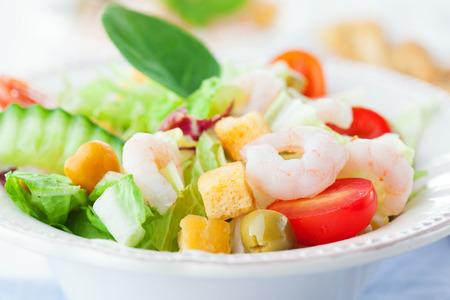 camaron: Ensalada de camarones con verduras sanas mixtos, aceitunas y tomates en el fondo de madera blanca, enfoque selectivo