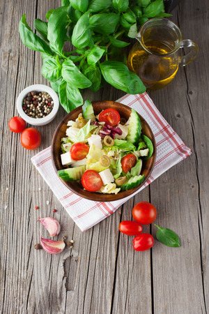 Fresh summer salad with cherry tomatoes, spinach, arugula, romaine and lettuce on dark wooden background, top view