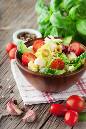 Fresh summer salad with cherry tomatoes, spinach, arugula, romaine and lettuce on dark wooden background, selective focus Stockfoto