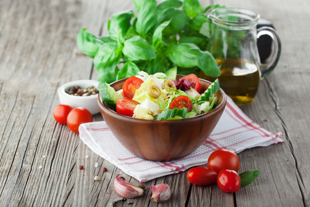 Fresh summer salad with cherry tomatoes, spinach, arugula, romaine and lettuce on dark wooden background, selective focus 스톡 콘텐츠
