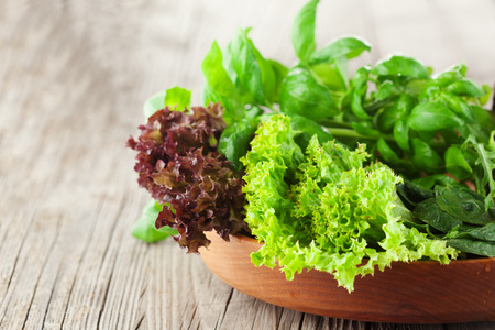 Mix of fresh salad - spinach, arugula, romaine and lettuce on rustic wooden background, selective focus