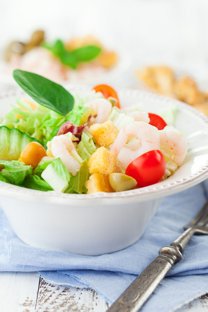 Healthy shrimp salad with mixed greens, olives and tomatoes on white wooden background, selective focus photo