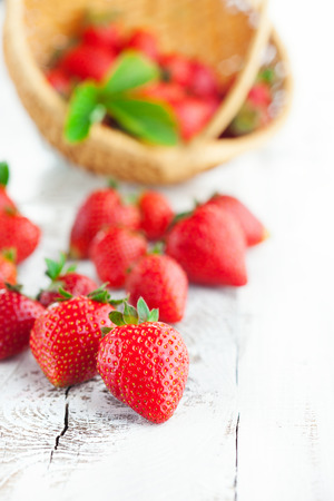 Juicy fresh strawberries in a basket on white wooden background, selective focus