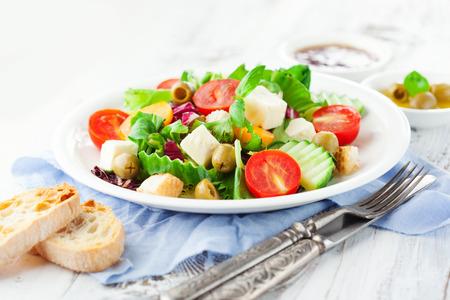 ensalada de tomate: Ensalada fresca del verano con tomates cherry, espinacas, rúcula, lechuga romana y lechuga en un plato sobre fondo de madera blanca, enfoque selectivo