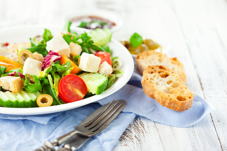 Fresh summer salad with cherry tomatoes, spinach, arugula, romaine and lettuces in a plate on white wooden background, selective focus