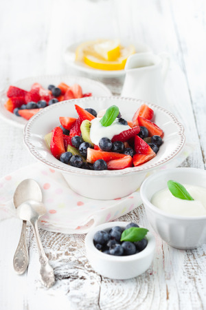 red white: Summer salad with ripe fresh fruits and berries on white wooden background, selective focus Stock Photo