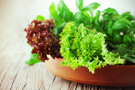 romaine: Mix of fresh salad - spinach, arugula, romaine and lettuce on rustic wooden background, selective focus