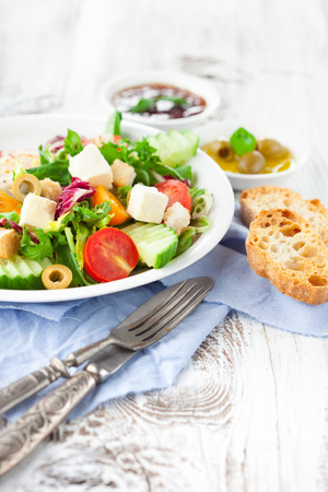 lettuces: Fresh summer salad with cherry tomatoes, spinach, arugula, romaine and lettuces in a plate on white wooden background, selective focus