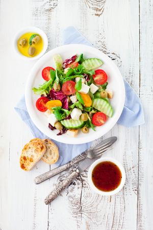 チェリー トマト、ほうれん草、ルッコラ、ロメイン レタス、レタスは、白い木製の背景、上面のプレートで新鮮な夏サラダ