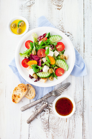Fresh summer salad with cherry tomatoes, spinach, arugula, romaine and lettuces in a plate on white wooden background, top view Stockfoto