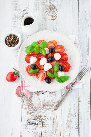 Ripe cherry tomatoes, fresh basil leaves, mozzarella cheese and olive oil for caprese salad on white wooden background, top view