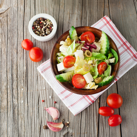 Fresh summer salad with cherry tomatoes, feta cheese and lettuce on rustic wooden background, top view