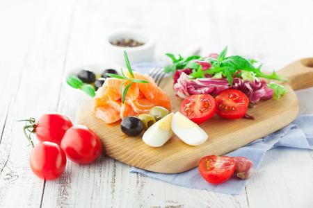 verduras verdes: Ingredientes para la ensalada con salmón, tomate cherry y lechuga en una tabla de cortar madera sobre fondo blanco rústico, enfoque selectivo Foto de archivo
