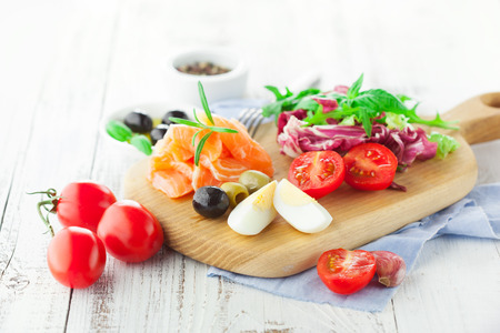 and raw: Ingredients for salad with salmon, cherry tomatoes and lettuce on a wooden chopping board on rustic white background, selective focus Stock Photo