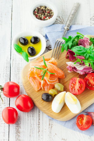 summer diet: Ingredients for salad with salmon, cherry tomatoes and lettuce on a wooden chopping board on rustic white background, top view
