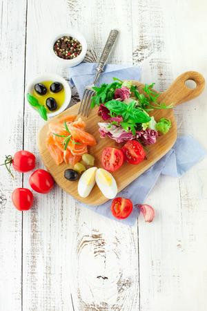 ensalada verde: Ingredientes para la ensalada con salm�n, tomate cherry y lechuga en una tabla de cortar madera sobre fondo blanco r�stico, vista desde arriba