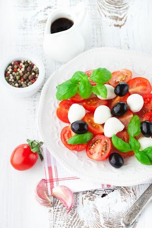 完熟チェリー トマト、バジルの葉、モッツアレラ チーズと白い木製の背景、トップ ビューでカプレーゼ サラダ オリーブ オイル