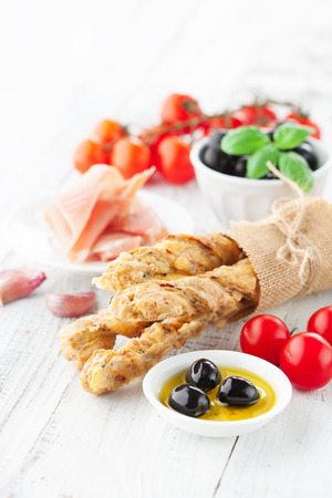 grissini: Grissini bread sticks with ham, olives, basil on white wooden background, selective focus