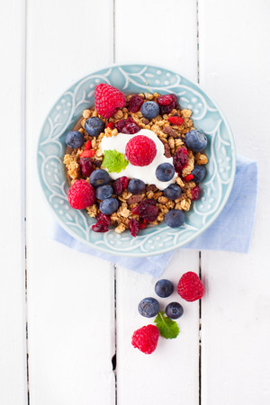 Healthy breakfast - muesli, milk and fresh berries on white wooden background, top view, health and diet concept photo