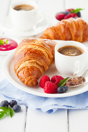 Breakfast with cup of coffee, fresh croissants and ripe berries on white wooden background, selective focus