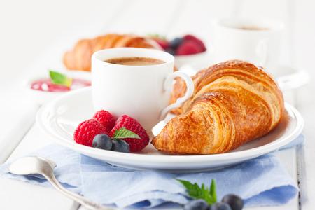 一杯のコーヒー、焼きたてのクロワッサン、白い木製の背景、選択と集中に熟した果実のブレックファストします。